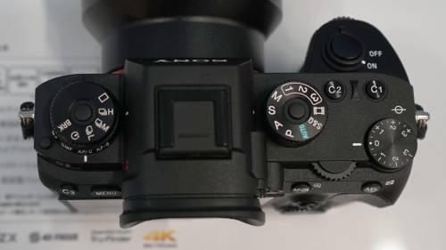 本体上面。左にドライブモード、右にモードダイヤル、露出補正ダイヤルを備える。露出補正以外は中央ボタンでロック解除