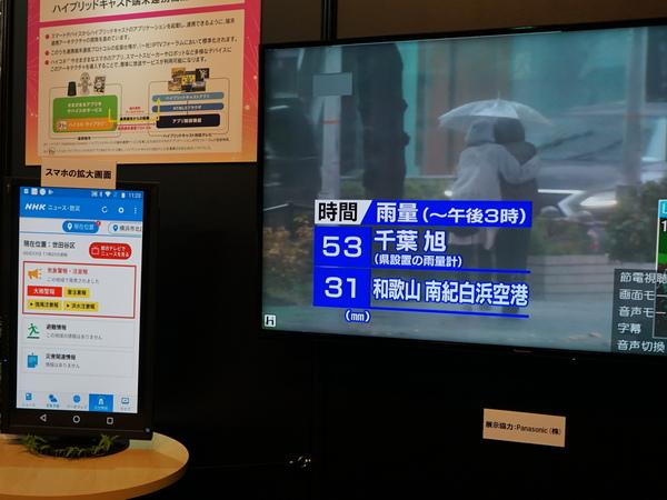 ハイブリッドキャストの端末連携の例。スマホ画面で災害警報などが出た際、「ニュースを見る」ボタンをタップするとテレビの電源が入って番組を表示する